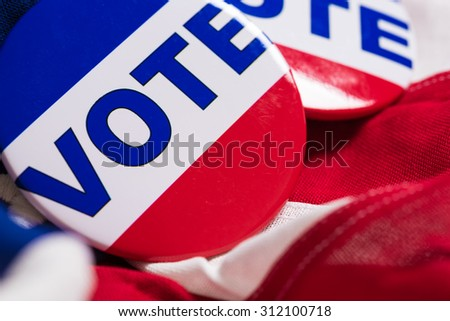 "A ""VOTE"" pin or button on a flag of the United States"