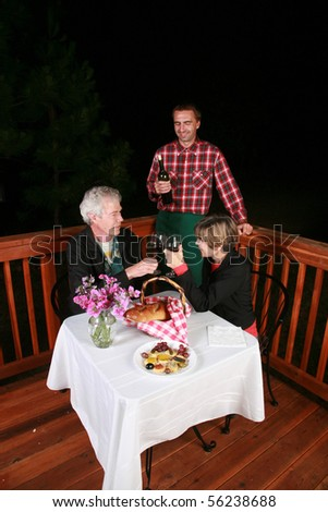 a waiter his customers at an outdoor cafe or bed and breakfast - stock photo