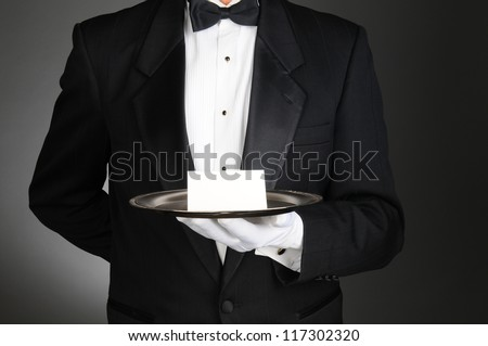 A waiter or butler wearing a tuxedo holding a note card on a silver tray in front of his torso. Man is unrecognizable over a light to dark gray background. - stock photo