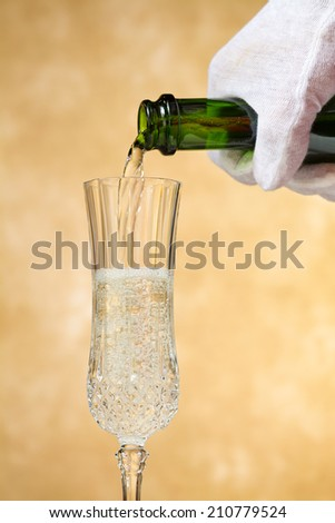 A waiter pours, crisp, delicious champagne into a stylish glass, poised against a golden, mottled background. - stock photo
