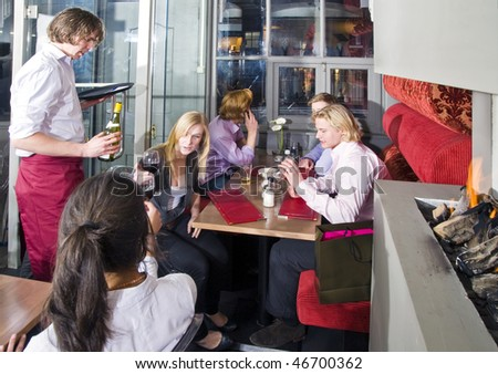 A waiter serving customers at tables in a trendy and crowded restaurant - stock photo