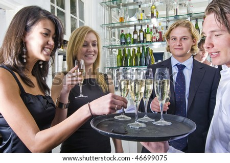 a waiter serving glasses of champagne on a tray in a restaurant - stock photo