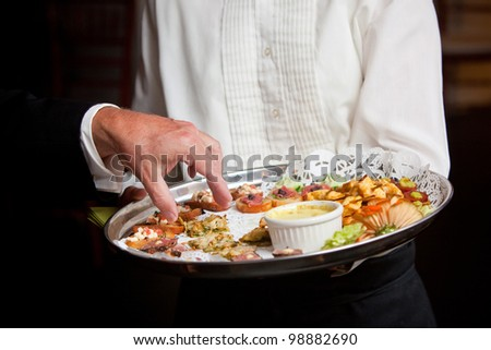 A waiter serving guests appetizers during a wedding or other catered event - stock photo