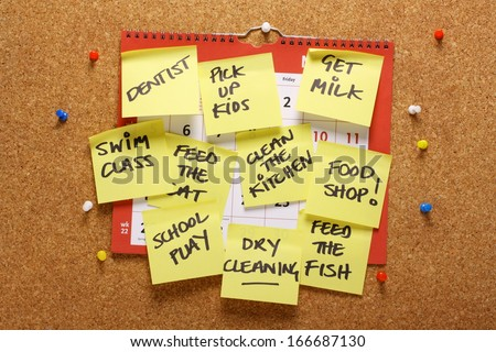 A wall calendar on a cork notice board covered with yellow sticky paper notes as a reminder of household chores and errands to be done. A concept for multitasking - stock photo