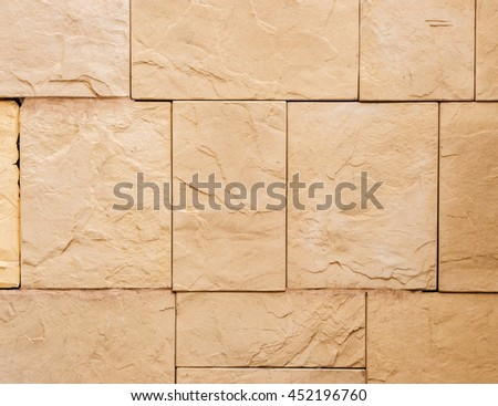 a wall from an artificial beige stone facade with rough fractured surfaces - stock photo