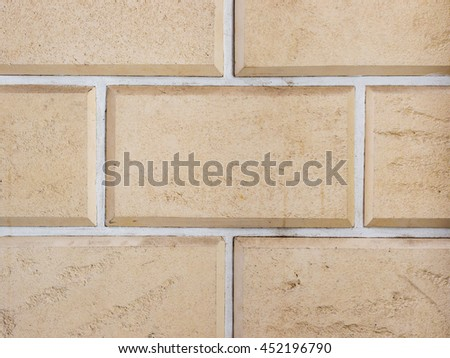 a wall from an artificial beige stone facade with rough fractured surfaces, laid as a brick - stock photo