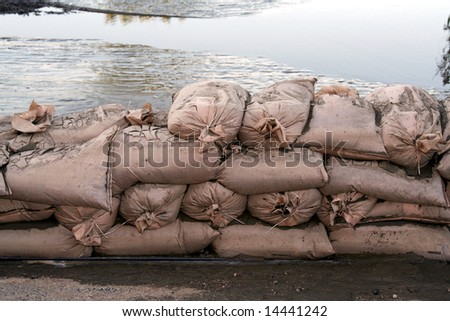 A wall of sandbags holds back floodwaters.