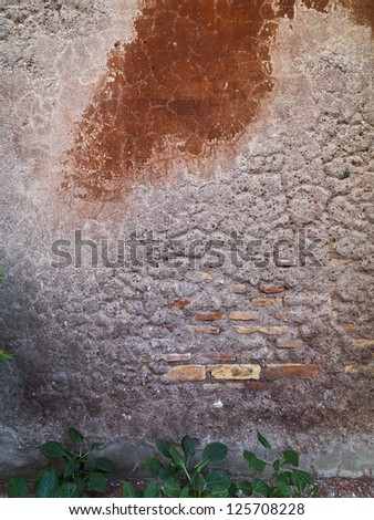 A wall that has been worn down to reveal bricks and cement - stock photo