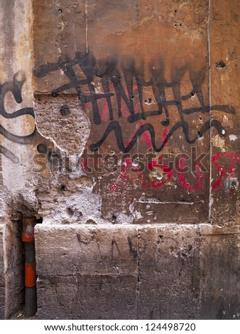 A wall with lots of graffiti and grime - stock photo