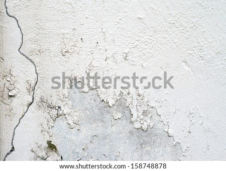 A wall with peeling plaster white color. - stock photo