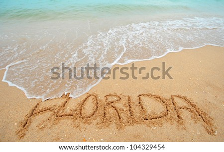 A warm tropical beach with blue water and waves and Florida written in the sand - stock photo
