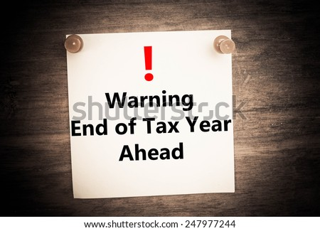 a warning of the end of the tax year ahead concept on note paper - stock photo