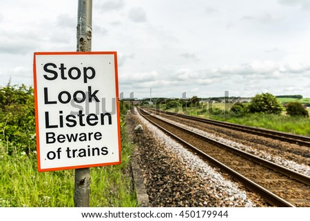 A warning sign cautions pedestrians at a crossing on a railway line with two train tracks. - stock photo