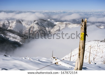 A warning sign marking the boundary between a ski area and a wide-open vista of Colorado mountains over clouds in winter. - stock photo