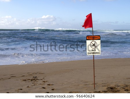A warning sign on Sunset Beach keeps swimmers out of the water with huge surf in the background - stock photo