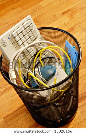 A waste basket full of used computer parts ready for the trash. - stock photo