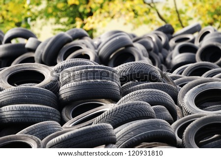 A waste heap of old tyres for rubber recycling - stock photo