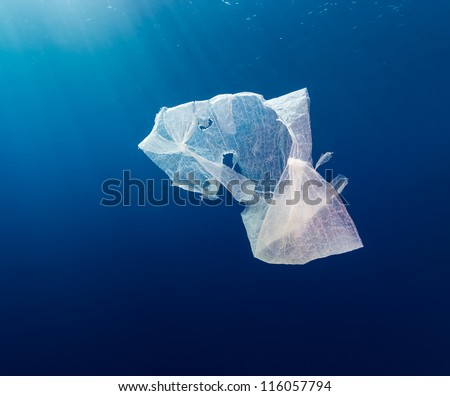A waste plastic bag floating in deep water in open ocean with sun rays behind - stock photo