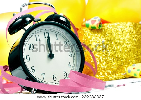 a watch at twelve, balloons, golden top hat, party horns, streamers and confetti for the new years party