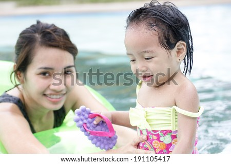 A watchful lady and a little girl in the swimming pool.