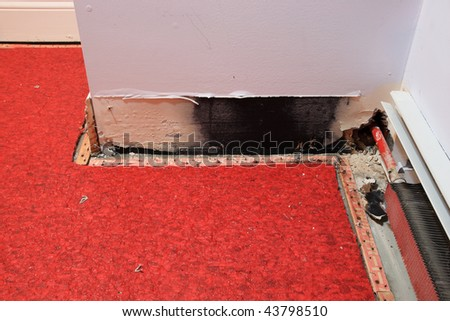 a water damaged wall from leaking pipe with carpet pulled back to dry - stock photo