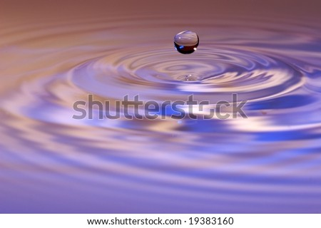 A water droplet rebounds into the air following a splash.