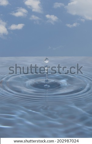 A water droplet with the sky in the background - stock photo
