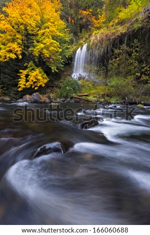 A water fall stumbles into the Sacramento River as the fall foliage takes on it's autumn color.  - stock photo