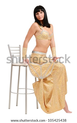 A water-nymph is sitting on high chair and holding in both hands her tail. Young woman is wearing shining top and skirt. - stock photo