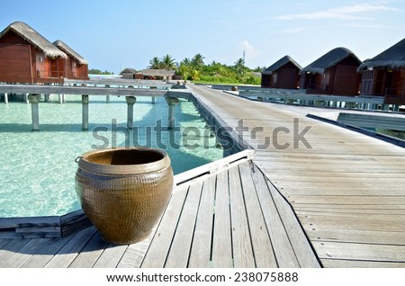 A water tank placed on the wooden road toward water villa in Maldives. It is used to clean the sands on feet when go back to the water villa - stock photo