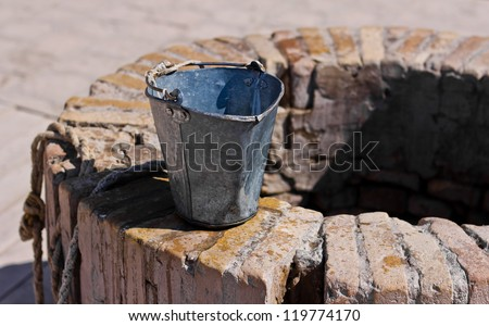 A water well with an old bucket in Samarkand, Uzbekistan - stock photo