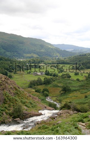 A waterfall flowing down into the valley of Grasmere in the Cumbrian Mountains in England's Lake District National Park. - stock photo
