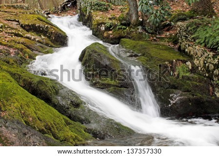 A waterfall flows around a rock in Tillman Ravine, Stokes State Forest, New Jersey. - stock photo