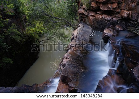 A waterfall flows into the depth in the majestic gorges of East Kimberley, Western Australia. - stock photo
