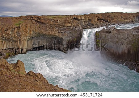 A waterfall in Iceland in the middle of the columnar basalt and volcanic rocks