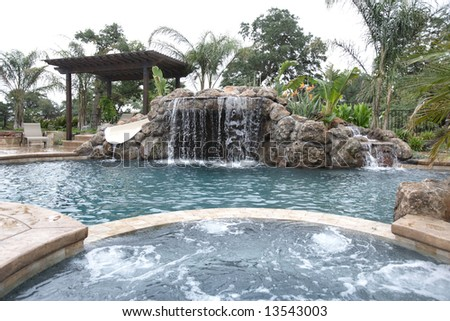 A waterfall in to a pool in a luxury backyard with tropical landscaping