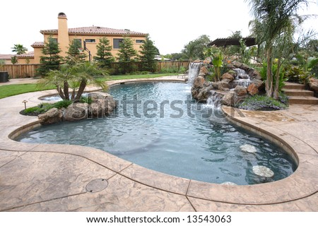 A waterfall in to a pool in a luxury backyard with tropical landscaping - stock photo