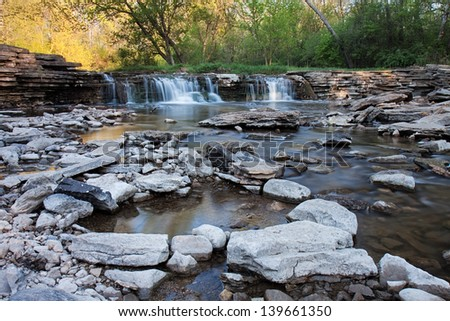 A waterfall supplies a rocky stream with an ample flow of springtime water. Along the stream, pools of water are formed reflecting the soft colors of the morning sunlit trees. - stock photo