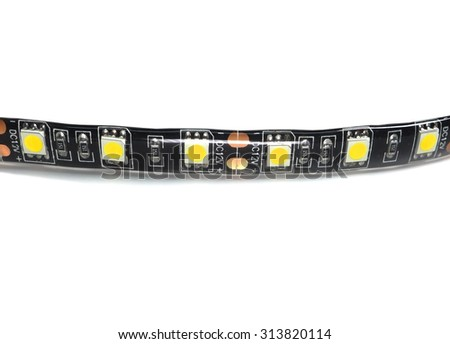 A waterproof LED strip with adhesive backing close up on white.