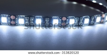 A waterproof LED strip with adhesive backing close while lit up - stock photo