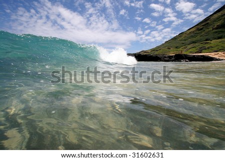 a wave breaking close to shore - stock photo