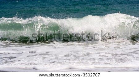 A wave crashing on the shore - stock photo