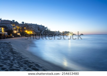 A wave lit by the bright moonlight rushes to the shore of a sandy cove with affluent homes.  - stock photo