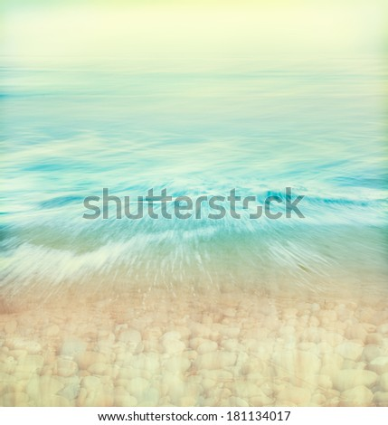 A wave of water washing over a rocky shoreline done with subtle retro colors.  Image made using panning motions combined with a long exposure.