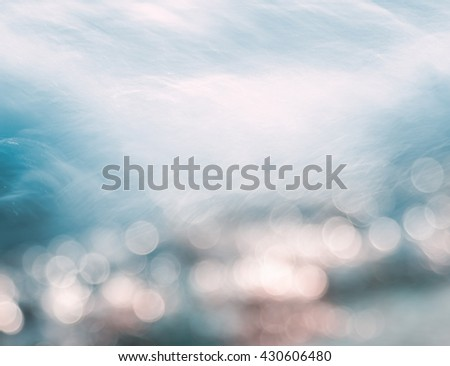 A wave splashing on the shore with bokeh light effects.  Image displays subtle cross-processing. - stock photo
