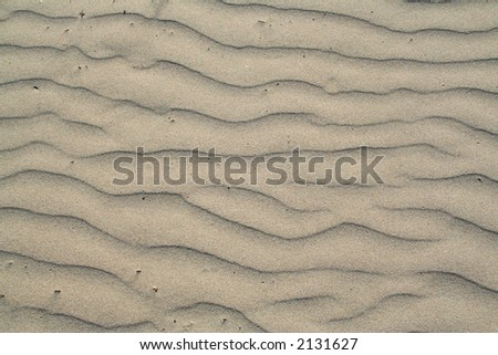 A wavy patter in the sand. - stock photo