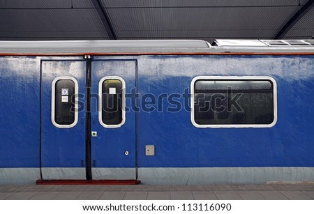 A weathered blue color electric train carriage with a sliding mechanical door at a train station platform. - stock photo