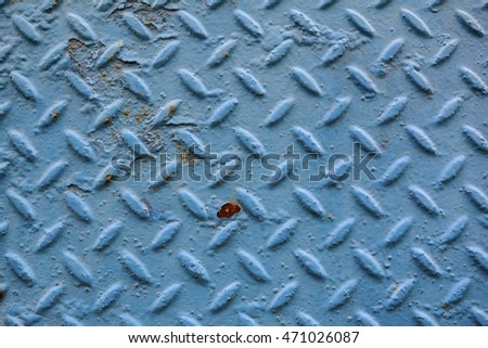 A weathered blue diamond plate background with flecks of rust