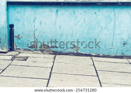 A weathered blue wall and a sloping pavement - stock photo