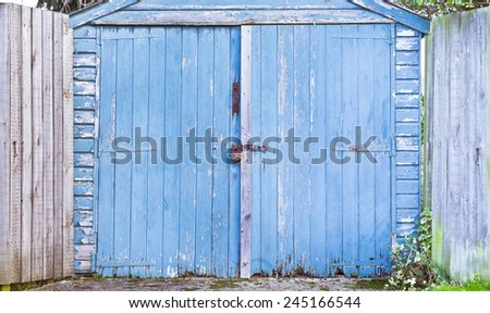 A weathered blue wooden garage door - stock photo